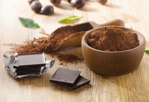 44713242 - chocolate bars and a wooden bowl of cacao powder. selective focus